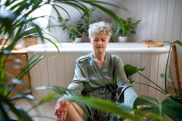 自宅のバスルームでヨガをしている年配の女性の肖像画、リラックスしてセルフケアの概念。