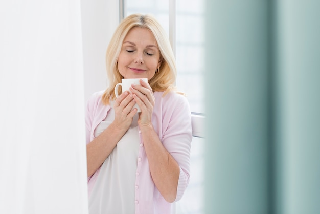 一杯のコーヒーを楽しんでいる年配の女性の肖像画