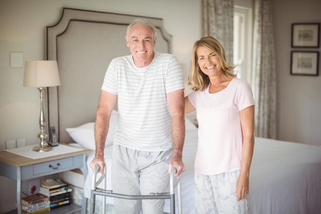 Портрет пожилой женщины, помогающей мужчине ходить с ходунками