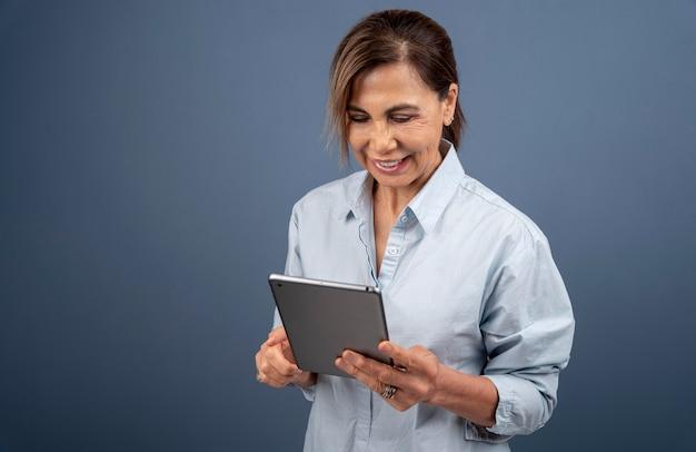 태블릿을 들고 수석 여자의 초상화 무료 사진
