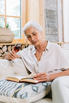 Portrait of senior woman holding glass of drink reading book