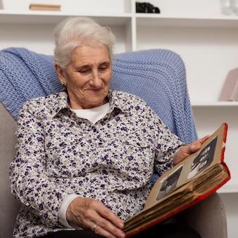 Портрет старшей женщины, держащей фотоальбом