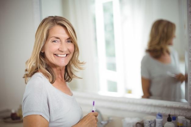 バスルームに歯ブラシを保持している年配の女性の肖像画