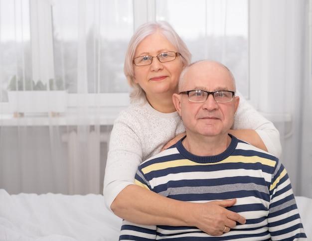 自宅で年配の男性を抱き締める年配の女性の肖像画