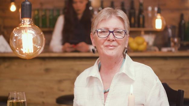 カメラを見ているレストランで年配の女性の肖像画。リラックスした老婆。 60代の女性。
