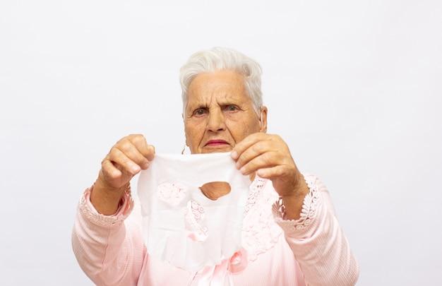 밝은 스튜디오 배경에서 원기를 회복시키는 면 마스크를 벗고 목욕 타월을 입은 고위 여성의 초상화. 노화 방지 화장품을 사용하는 사랑스러운 중년 여성 화장품 마스크 사용법