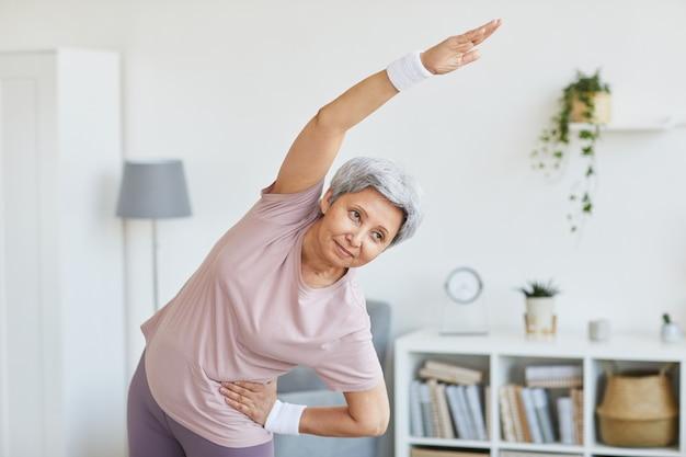 Портрет пожилой женщины в спортивной одежде, делающей упражнения в гостиной дома