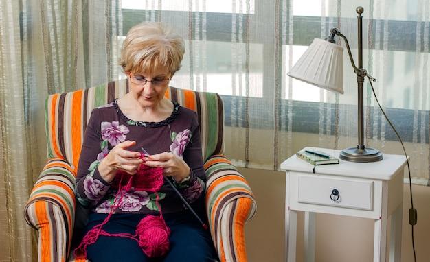 집에서 모직 스웨터를 뜨개질하는 노인 여성의 초상화