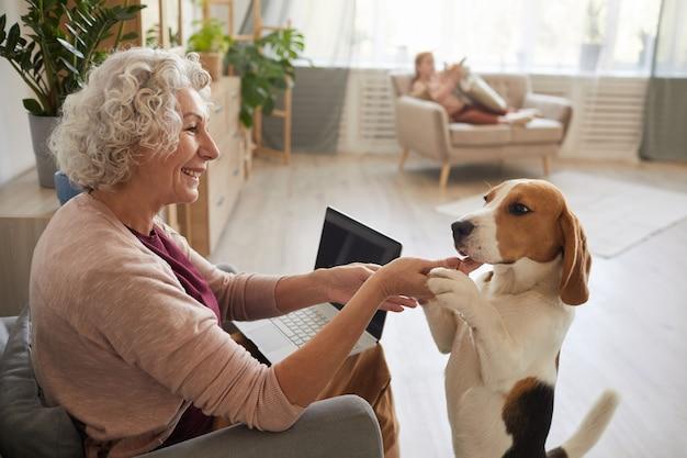 Портрет пожилой женщины, играющей с собакой, наслаждаясь временем дома в уютном интерьере