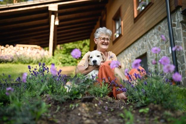 Портрет старшей женщины, сидящей на открытом воздухе в саду, концепция дружбы собак.