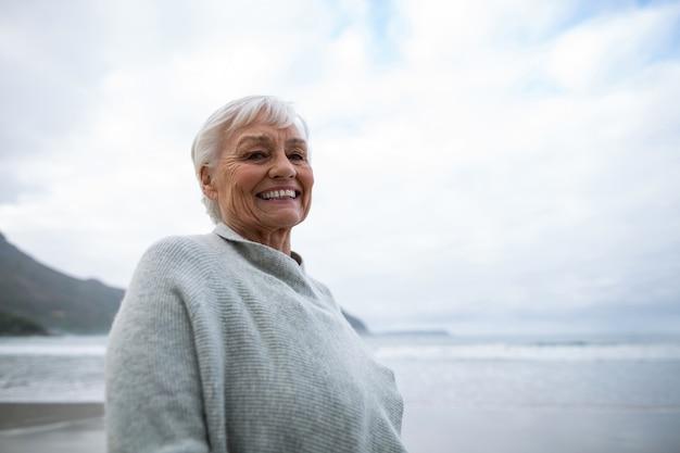 Портрет старшей женщины стоя на пляже