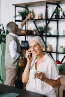 Portrait of senior woman talking on cell phone holding coffee cup