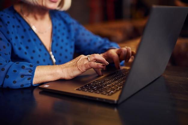 現代のラップトップでカフェの屋内に座っている年配の女性の肖像画。