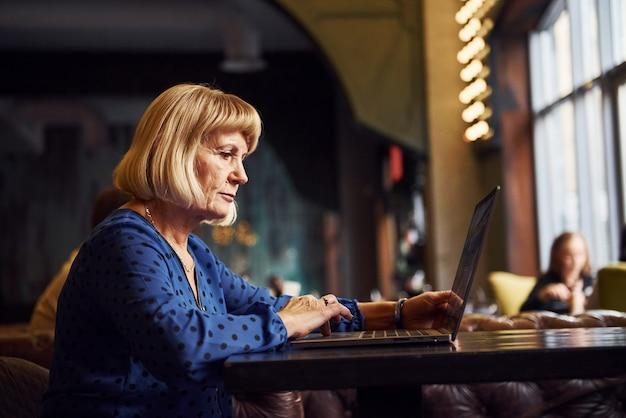 Портрет старшей женщины, которая сидит в помещении в кафе с современным ноутбуком.