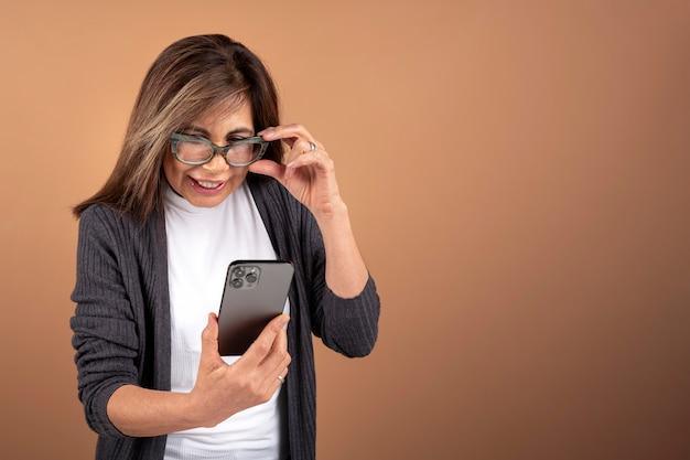 Портрет старшей женщины, использующей свой смартфон