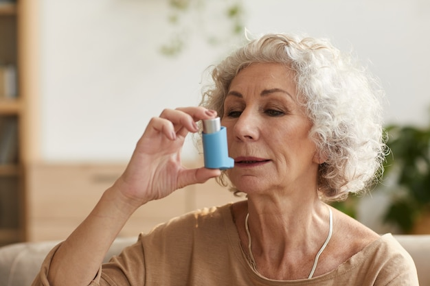Портрет пожилой женщины, использующей ингалятор для лечения астмы или проблем с дыханием в домашних условиях