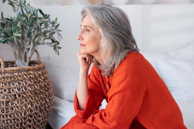 赤いシャツを着ている年配の女性の肖像画