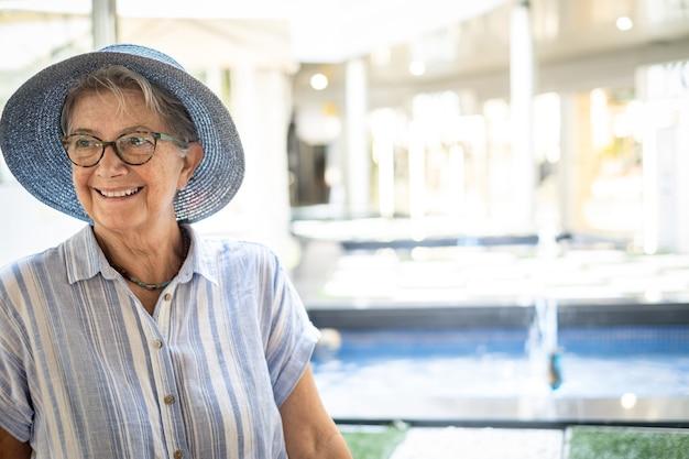 笑顔のショッピングモールに座って麦わら帽子をかぶった年配の女性の肖像画