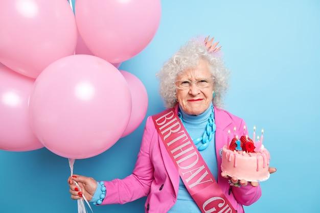 灰色の巻き毛を持つ年配の女性のポートレートは、不満そうな顔の表情をし、お祝いの服を着て、誕生日を祝い、おいしいケーキを膨らませた風船の束を持っている Premium写真