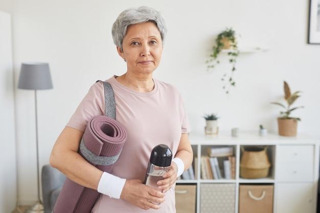 Портрет пожилой женщины с седыми волосами, держащей бутылку воды и коврик для упражнений