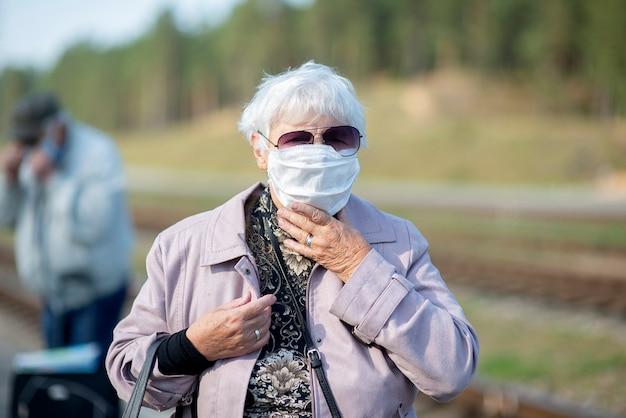 Портрет пожилой женщины с медицинской маской на лице, профилактика вирусов и инфекций