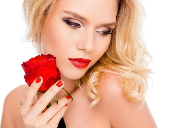 彼女の手に赤いバラを持つ官能的な魅力的な女性の肖像画
