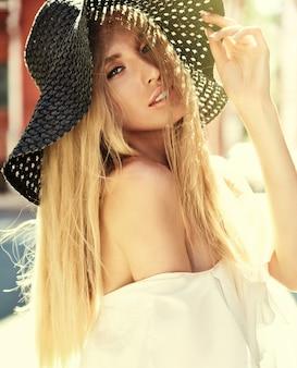 Портрет чувственной блондинки модели, одетой в белое платье и летняя пляжная шляпа позирует на фоне улицы за закатом