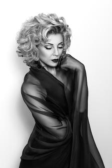 ショールを身に着けている官能的な成熟した思慮深い女性の肖像画。黒と白の写真。