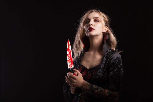 ハロウィーンのカーニバルのためにドレスアップした官能的な吸血鬼の女性の肖像画。ゴージャスな吸血鬼の女性。