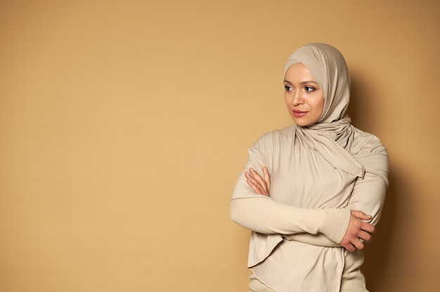 ヒジャーブとベージュの伝統的なフォーマルドレスを着た穏やかな美しいイスラム教徒の女性の肖像画は、横を向いて、コピースペースのあるベージュの表面で彼女の前で腕を組んでいます