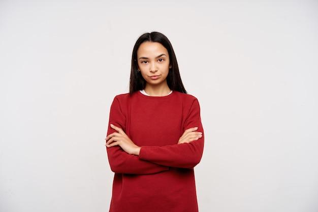 暗い長い髪の深刻な、大人のアジアの女の子の肖像画。赤いセーターを着て、胸に交差した腕を折ります。白い背景の上に隔離されたカメラの非難を見て