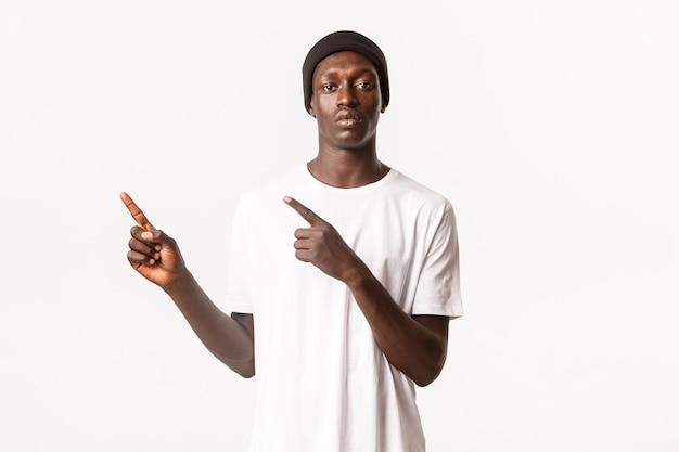 Портрет серьезного афро-американского парня в шапочке, указывая пальцами в верхнем левом углу, показывая логотип