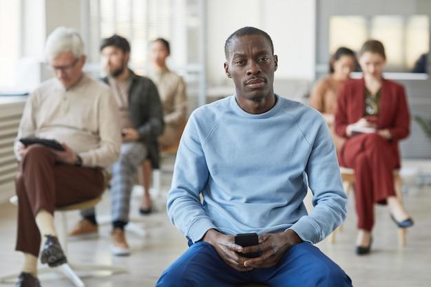 Портрет серьезного афроамериканца, смотрящего в камеру, позируя в офисе с разнообразной группой людей на заднем плане, копией пространства