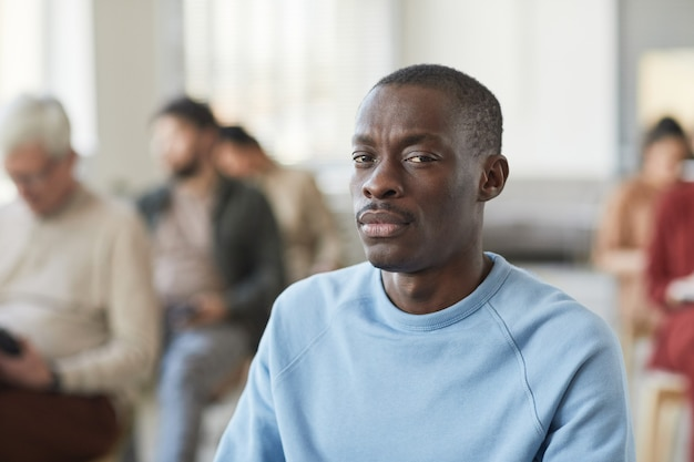 Портрет серьезного афроамериканца, смотрящего в камеру, сидя в аудитории с разнообразной группой людей на заднем плане, копией пространства