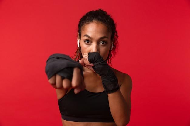 彼女の手にスポーツ包帯、赤い壁に隔離された黒いスポーツウェアボクシングの深刻なアフリカ系アメリカ人女性の肖像画