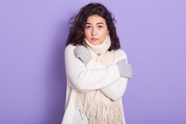 カメラを直接見て、腕を組んで、白いセーターを着ている黒い巻き毛の深刻な魅力的な女性の肖像画