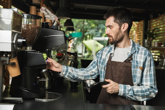 ストリートカフェや屋外の喫茶店で働いている間コーヒーを作るエプロンを身に着けている深刻なバリスタ男の肖像画