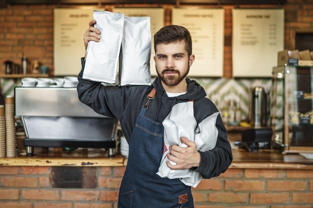 Портрет серьезного бородатого фартука бариста в фартуке с мешком кофе