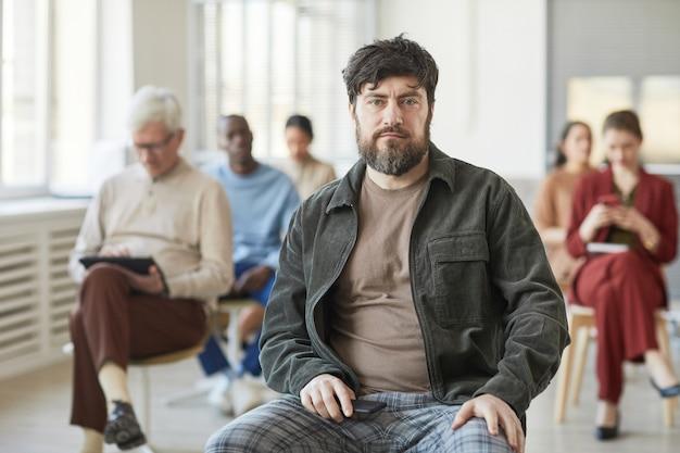 Портрет серьезного бородатого мужчины, одетого в повседневную одежду и смотрящего в камеру, позируя в офисе с разнообразной группой людей на заднем плане, копией пространства