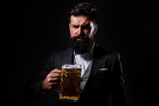 ビールを飲む深刻なひげを生やした男の肖像画。ビールとグラスを持って幸せな醸造所。