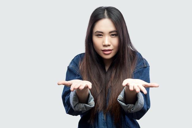 Портрет молодой женщины серьезного красивого брюнет азиатской в вскользь голубой джинсовой куртке при макияж стоя поднял оружия и смотря камеру. крытая студия выстрел, изолированные на светло-сером фоне.