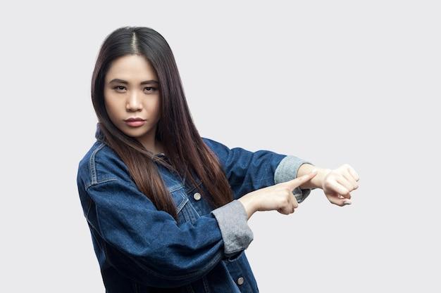 Портрет молодой женщины серьезного красивого брюнет азиатской в вскользь голубой куртке с косметикой стоя и показывая жест времени или вахты в наличии. крытая студия выстрел, изолированные на светло-сером фоне.