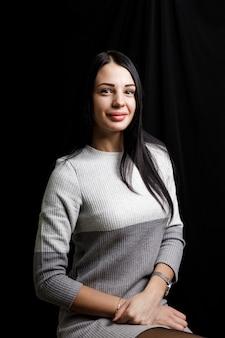 Портрет серьезной красивой женщины с черными волосами, с минимальным макияжем, спокойно смотрит в камеру, в белом джемпере, стоит на фоне черного пространства, задумавшись.