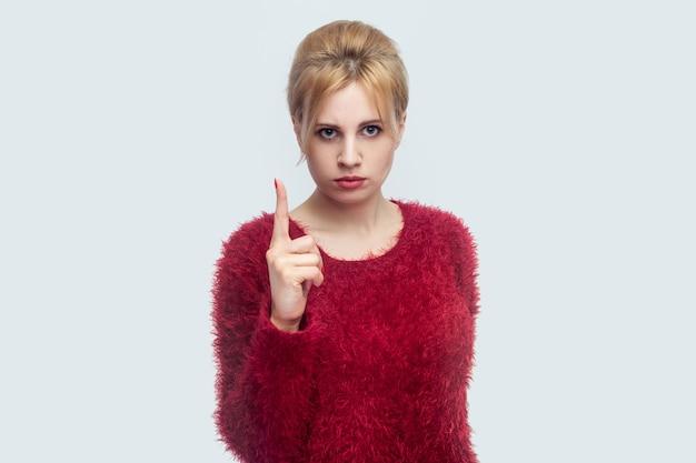 Портрет серьезной красивой молодой белокурой женщины в красной блузке, стоящей и смотрящей в камеру с предупреждающим пальцем и тревожной. закрытая студия выстрел, изолированные на светло-сером фоне.
