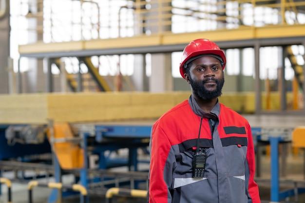 くびれ工場で働くジャケットにトランシーバーデバイスを持つ深刻な黒人労働者の肖像画