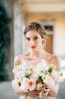 Портрет серьезной невесты в платье с букетом розовых цветов