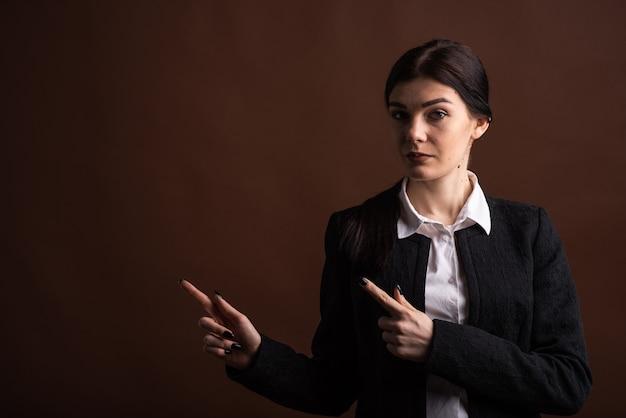 Copyspace와 갈색 배경에 스튜디오에서 그녀의 손가락을 가리키는 심각한 갈색 머리 비즈니스 여자의 초상화