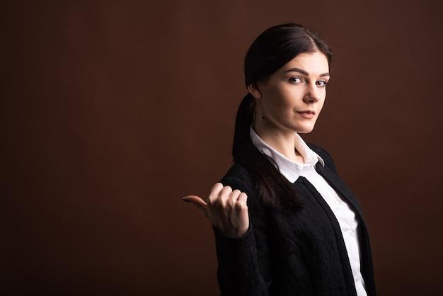 Copyspace와 갈색 배경에 스튜디오에서 측면에 그녀의 엄지 손가락을 가리키는 심각한 갈색 머리 비즈니스 여자의 초상화