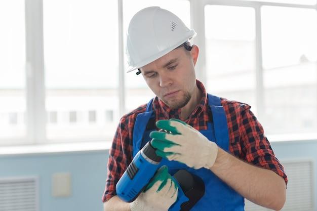 드릴 흰색 헬멧을 쓰고 심각한 작성기 남자의 초상화.