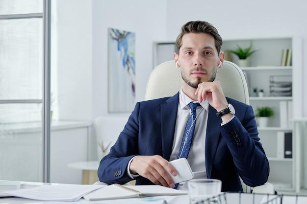 机に座って、オフィスで現代の電話を保持しているイヤホンで真面目なビジネスマネージャーの肖像画